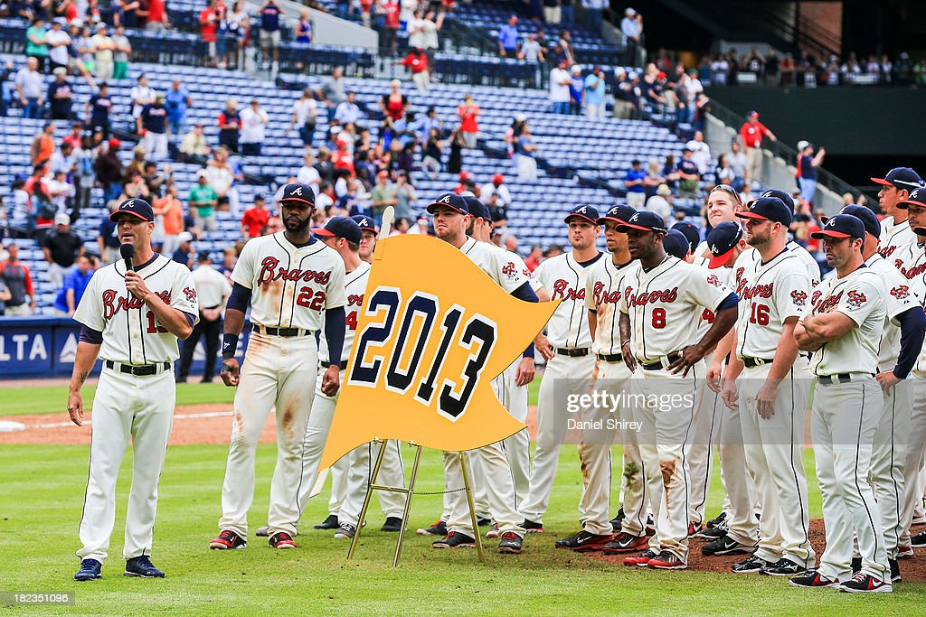 Tim Hudson of the Atlanta Braves and teammates present their 2013 pennant to fans after beating the Philadelphia Phillies at Turner Field on...