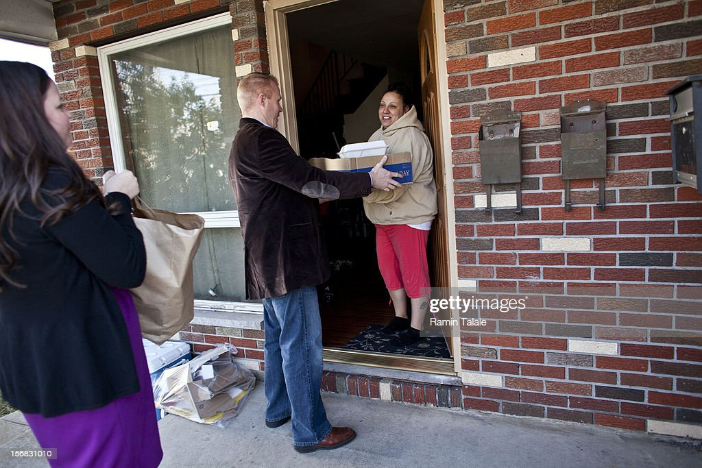 Tim Hynes (C) and his wife Laura Hynes (L) deliver prepared Thanksgiving meals from Saint Charles Church to Angela Ng, one of the victims of Superstorm Sandy, on November 22, 2012 in the Staten Island borough of New York City. Sections of Staten Island were hard hit by flooding from Superstorm Sandy.
