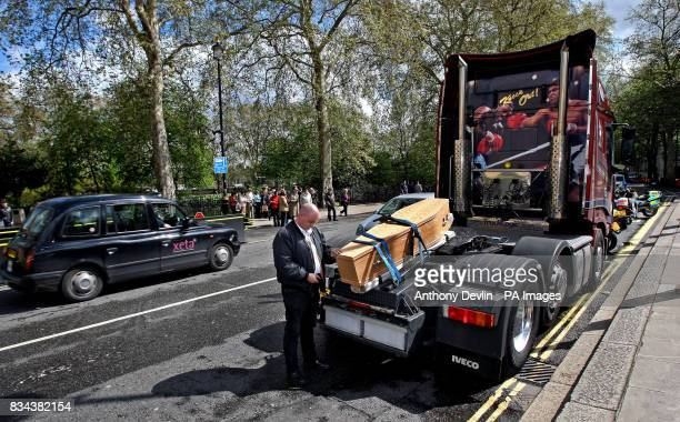 Tim Ingram from Transaction 2007 bows his head beside a coffin on a lorry outside the Houses of Parliament London as part of a protest against...