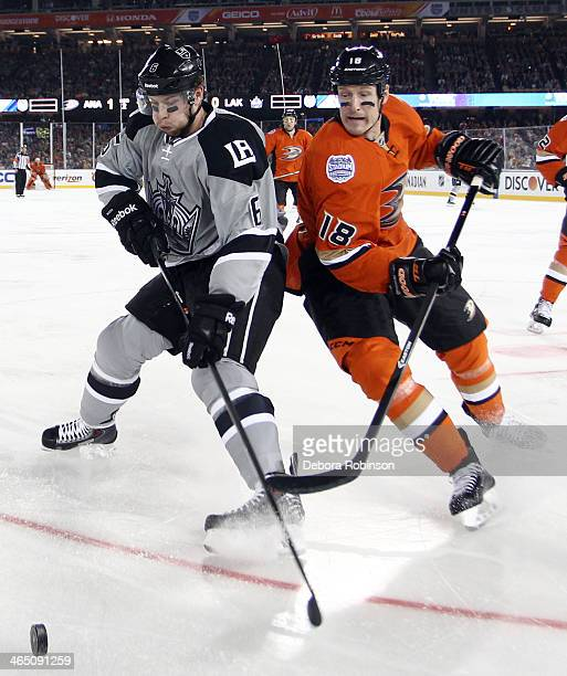 Tim Jackman of the Anaheim Ducks battles for the puck against Jake Muzzin of the Los Angeles Kings during the 2014 Coors Light NHL Stadium Series on...