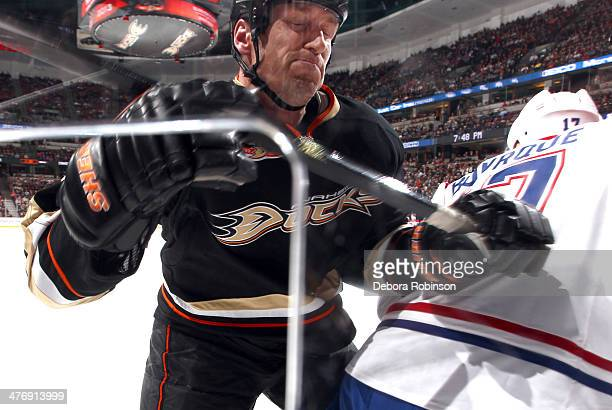 Tim Jackman of the Anaheim Ducks checks Rene Bourque of the Montreal Canadiens into the boards on March 5 2014 at Honda Center in Anaheim California