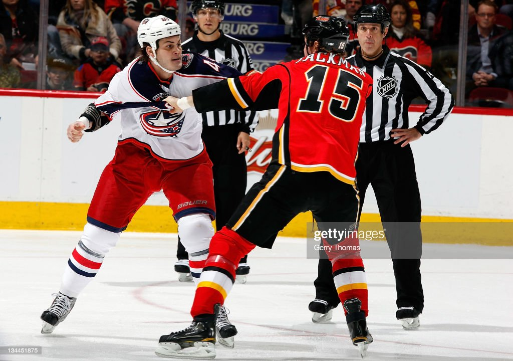 Tim Jackman of the Calgary Flames exchange punches with Jared Boll of the Columbus Blue Jackets on December 1 2011 at the Scotiabank Saddledome in...