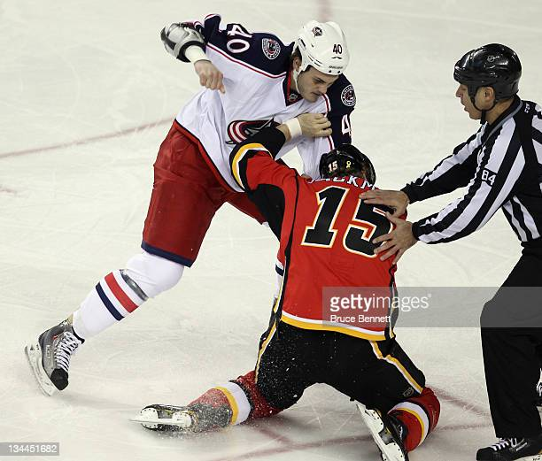 Tim Jackman of the Calgary Flames fights with Jared Boll of the Columbus Blue Jackets during the first period at the Scotiabank Saddledome on...