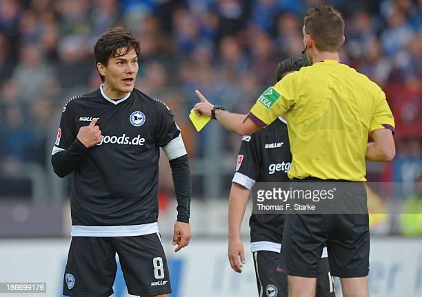 Tim Jerat of Bielefeld argues with referee Christian Bandurski during the Second Bundesliga match between Karslruher SC and Arminia Bielefeld at...