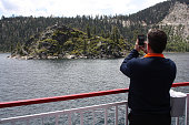 Tim Jung of Lincoln Neb uses his smartphone to capture Fannette Island as the tour boat MS Dixie II heads westward inside Lake Tahoe's Emerald Bay
