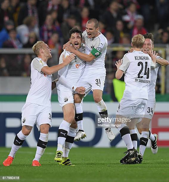 Tim Kister of Sandhausen celebrates with his teammates after scoring his team's first goal during the DFB Cup match between SC Freiburg and SV...
