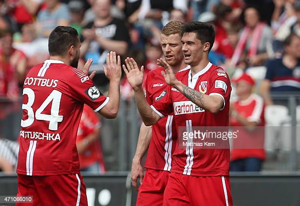 Tim Kleindienst of Cottbus jubilates with team mate Uwe Moehrle and Torsten Mattuschka after scoring the second goal during the third league match...
