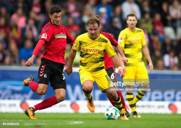 Tim Kleindienst of Freiburg and Mario Goetze of Dortmund fight for the ball during the Bundesliga match between SportClub Freiburg and Borussia...