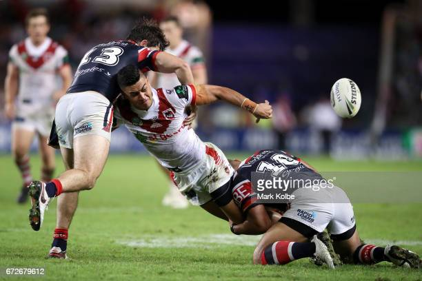 Tim Lafai of the Dragons passes as he is tackled by Aidan Guerra and Isaac Liu of the Roosters during the round eight NRL match between the Sydney...