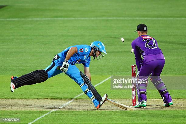 Tim Ludeman of the Adelaide Strikers makes his ground in front of Tim Paine of the Hobart Hurricanes during the Big Bash League match between the...