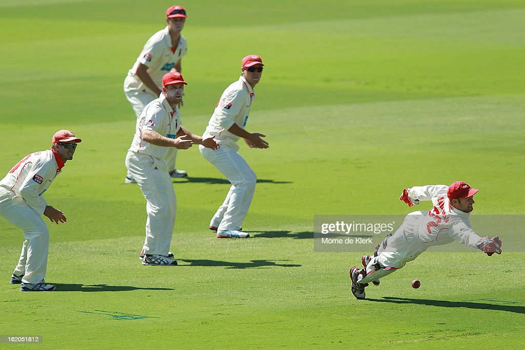 Tim Ludeman (R) of the Redbacks dives but fails to make a stop as Redbacks players look on during day one of the Sheffield Shield match between the South Australian Redbacks and the New South Wales Blues at Adelaide Oval on February 19, 2013 in Adelaide, Australia.