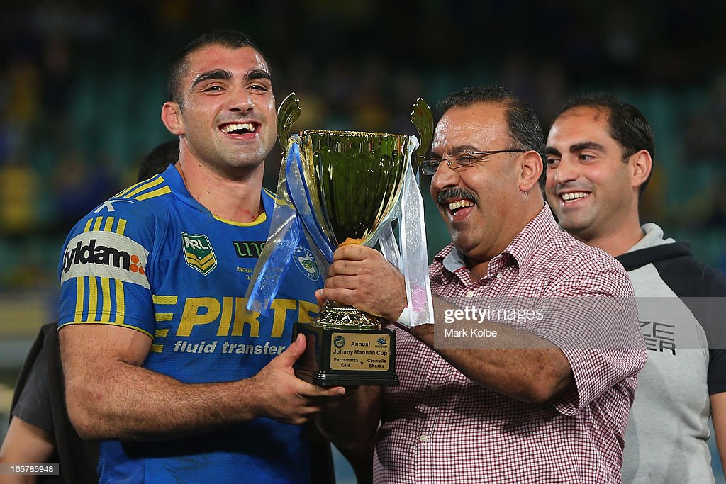 Tim Mannah and his father Fred Mannah share a laugh as they pose with the Annual Johnny Mannah cup after the round five NRL match between the Parramatta Eels and the Cronulla Sharks at Parramatta Stadium on April 6, 2013 in Sydney, Australia.