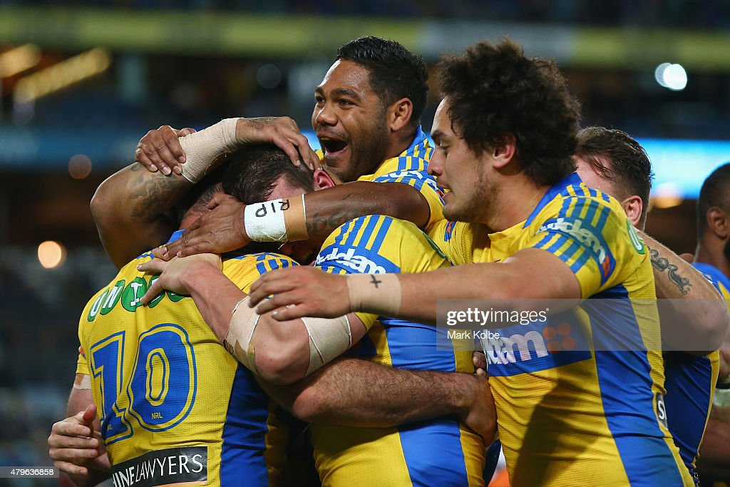 Tim Mannah of the Eels celebrates with his team mates Chris Sandow and Brad Takairangi of the Eels after scoring a try during the round 17 NRL match between the Wests Tigers and the Parramatta Eels at ANZ Stadium on July 6, 2015 in Sydney, Australia.