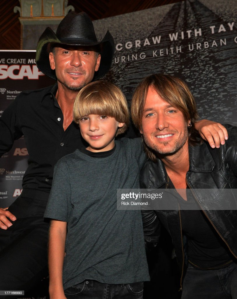 Tim McGraw and Keith Urban along with a young fan attend as Tim McGraw Celebrates Multi-Week No. 1 'Highway Don't Care' at Music City Tippler on August 20, 2013 in Nashville City.