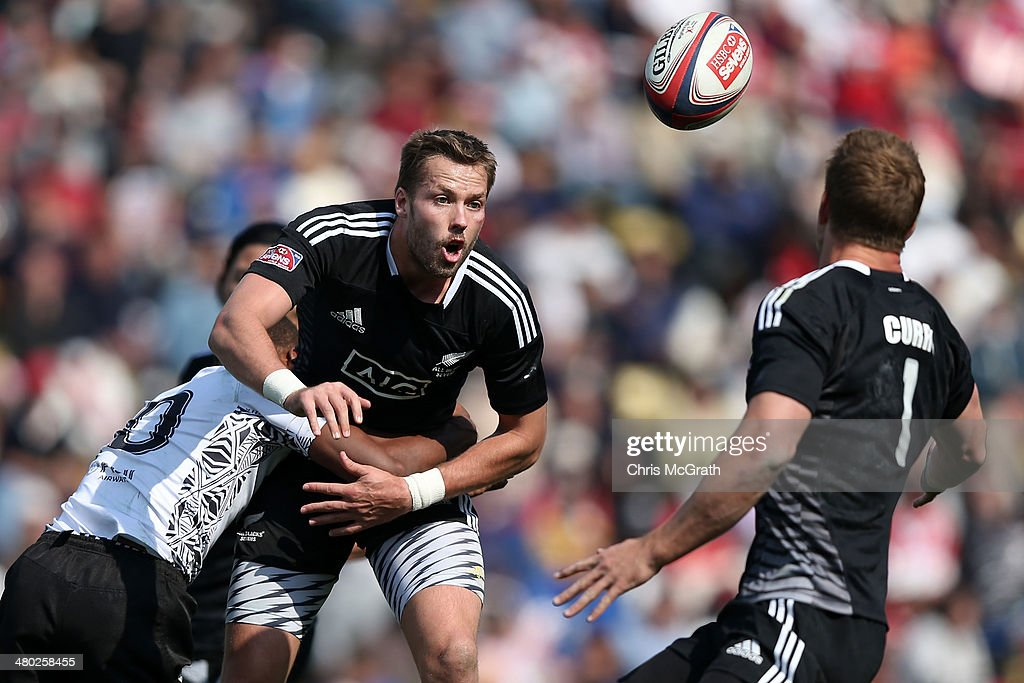 Tim Mikkelson #2 of New Zealand gets a pass away under pressure from Osea Kolinisau #10 of Fiji during the Tokyo Sevens, in the six round of the HSBC Sevens World Series at the Prince Chichibu Memorial Ground on March 23, 2014 in Tokyo, Japan.