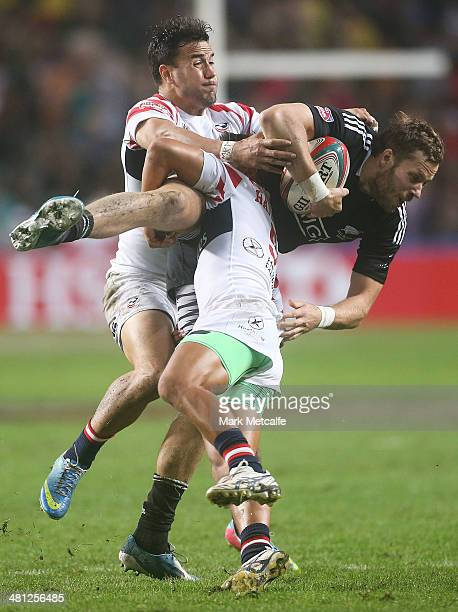 Tim Mikkelson of New Zealand is tackled during the Pool D match between New Zealand and the United States during day two of the 2014 Hong Kong Sevens...