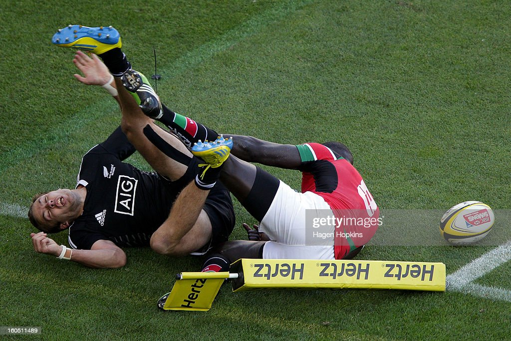 Tim Mikkelson of New Zealand scores a try in the tackle of Andrew Amonde of Kenya in the semifinal cup match between New Zealand and Kenya during the 2013 Wellington Sevens at Westpac Stadium on February 2, 2013 in Wellington, New Zealand.