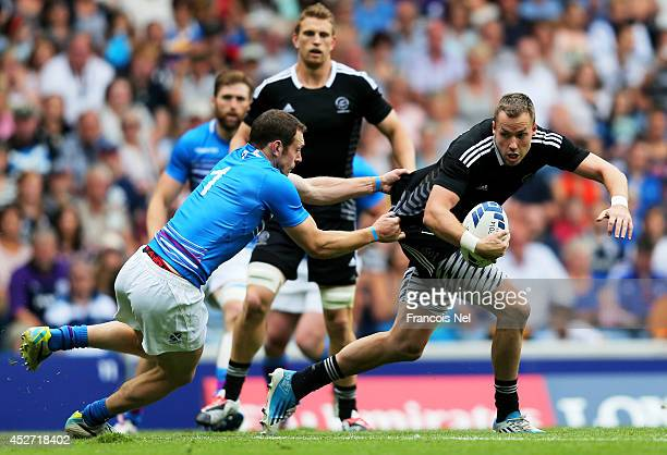 Tim Mikkleson of New Zealand is tackled by Scott Riddell of Scotland in the Rugby Sevens match between New Zealand and Scotland at Ibrox Stadium...