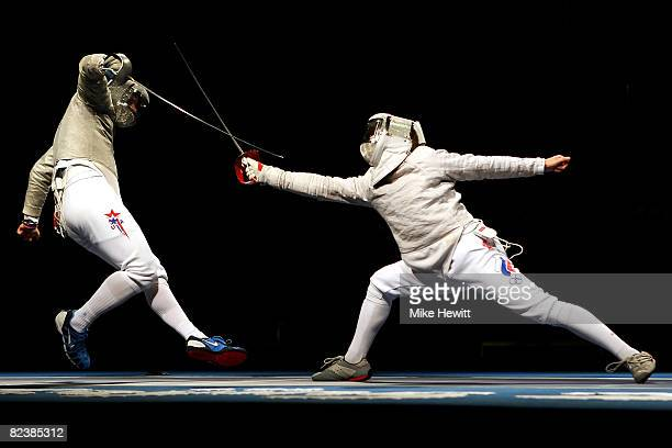 Tim Morehouse of the United States and Nikolay Kovalev of Russia compete in the men's team sabre fencing semifinals at the Fencing Hall of National...