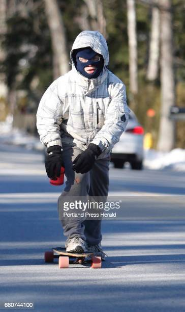 Tim Moulton is covered against the cold as he skateboards with his coffee down Temple Avenue towards the beach Friday morning