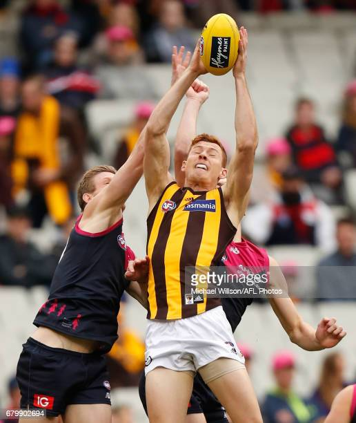 Tim O'Brien of the Hawks marks ahead of Sam Frost of the Demons during the 2017 AFL round 07 match between the Melbourne Demons and the Hawthorn...