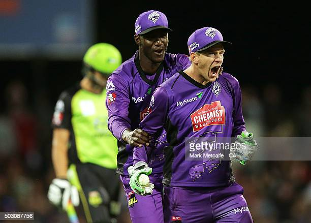 Tim Paine of the Hurricanes celebrates with team mates after taking the wicket of Chris Green of the Thunder during the Big Bash League match between...