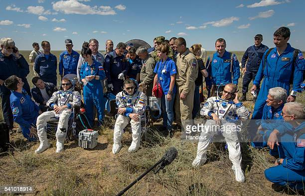 Tim Peake of the European Space Agency Yuri Malenchenko of Roscosmos and Tim Kopra of NASA sit in chairs outside the Soyuz TMA19M spacecraft just...