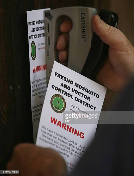Tim Phillips assistant manager and biologist with the Fresno Mosquito and Vector Control District staples a notice after he has inspected and treated...