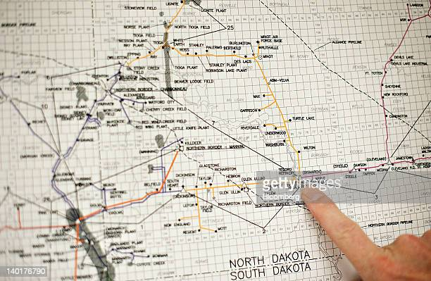 Tim Rasmussen public relations manager at MDU Resources Group Inc points to the city of Bismarck while discussing a map for the network of pipeline...