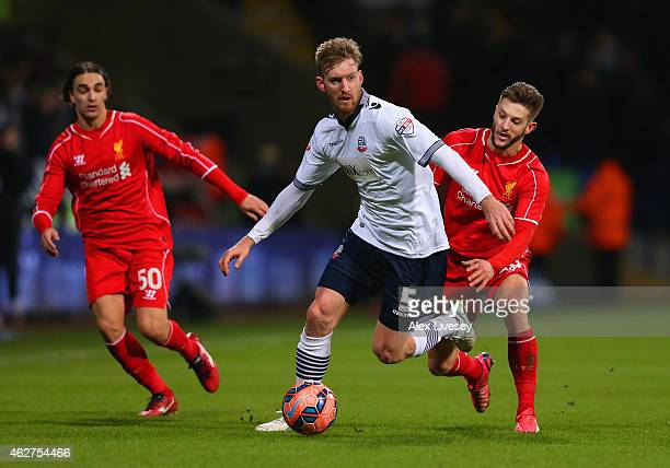 Tim Ream of Bolton Wanderers is marshalled by Adam Lallana of Liverpool during the FA Cup Fourth round replay between Bolton Wanderers and Liverpool...