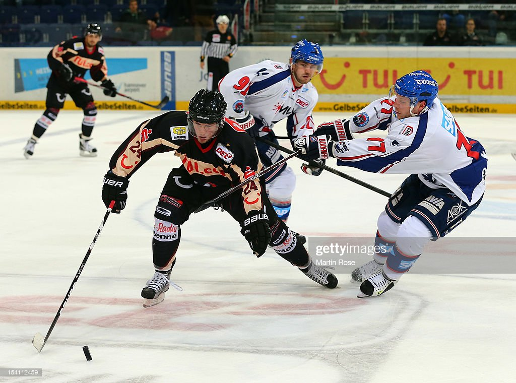 Tim Richter (L) of Hannover and Marcus Kink (R) of Mannheim battle for the puck during the DEL match between Hannover Scorpions and Aadler Mannheim at TUI Arena on October 14, 2012 in Hanover, Germany.