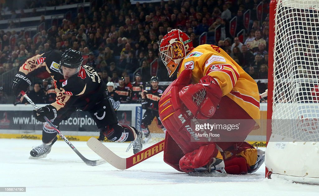 Tim Richter (L) of Hannover fails to score over Robert Goepfert (R), goaltender of Duesseldorf during the DEL match between Hannover Scorpions and Duesseldorfer EG at TUI Arena on November 23, 2012 in Hanover, Germany.