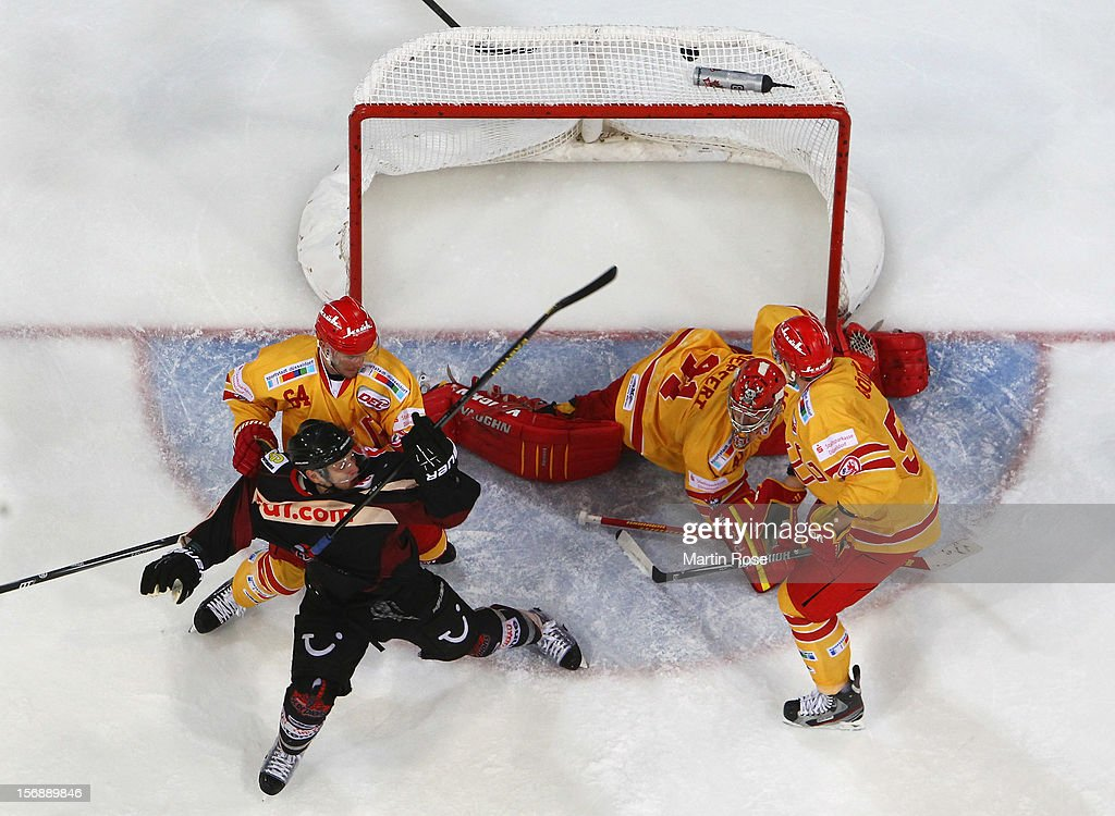 Tim Richter (C) of Hannover fails to score over Robert Goepfert (C), goaltender of Duesseldorf during the DEL match between Hannover Scorpions and Duesseldorfer EG at TUI Arena on November 23, 2012 in Hanover, Germany.