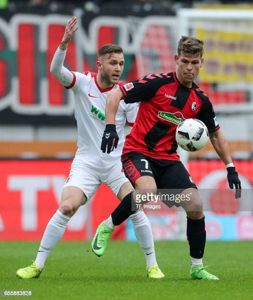 Tim Rieder of Augsburg and Florian Niederlechner of Freiburg battle for the ball during the Bundesliga match between FC Augsburg and SC Freiburg at...