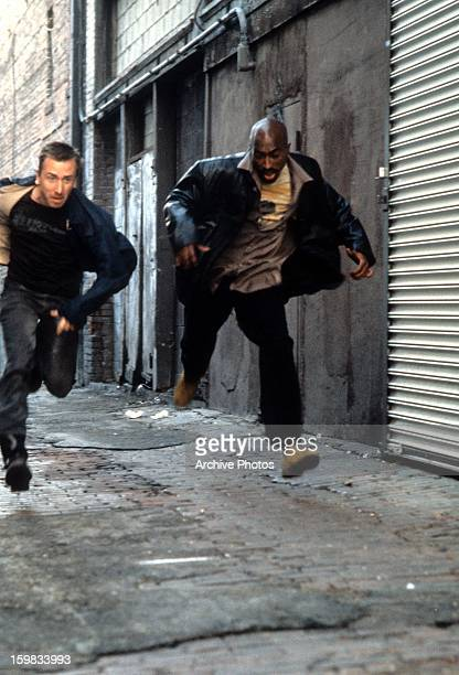 Tim Roth and Tupac Shakur run down an alley in a scene from the film 'Gridlock'd' 1997