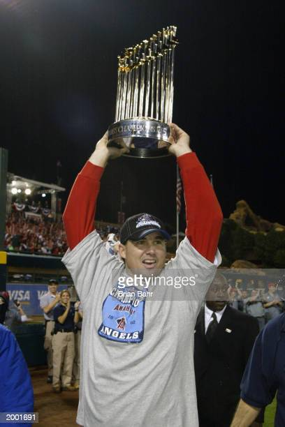 Tim Salmon of the Anaheim Angels holds the World Series trophy above his head as he circles the field after the victory over the San Francisco Giants...