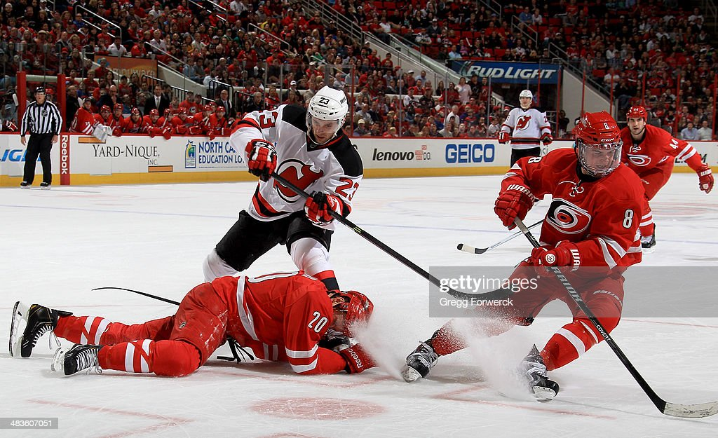 Tim Sestito of the New Jersey Devils attempts to make a pass as Riley Nash of the Carolina Hurricanes goes down on the ice to block the puck as he...