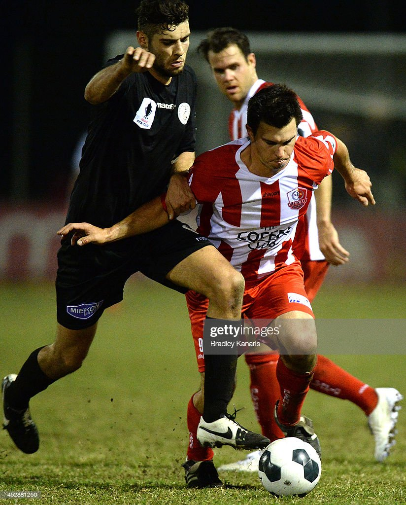 Tim Smits of Olympic is challenged by the defence of Tomislav Uskok of the Knights during the FFA Cup match between Olympic FC and Melbourne Knights at Goodwin Park on July 29, 2014 in Brisbane, Australia.