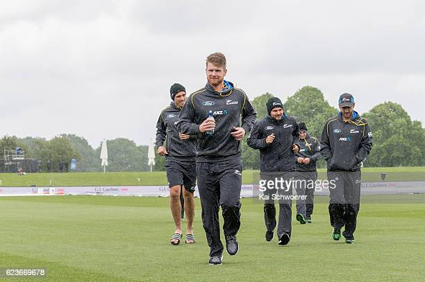 Tim Southee James Neesham Head Coach Mike Hesson and Kane Williamson of New Zealand run from the ground as rain delays play during day one of the...