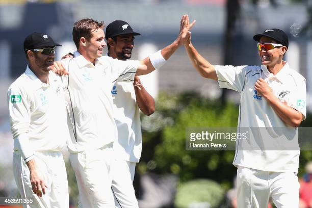 Tim Southee of New Zealand celebrates the wicket of Narsingh Deonarine of the West Indies with Aaron Redmond Ish Sodhi and Trent Boult during day...