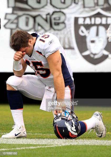Tim Tebow of the Denver Broncos kneels on the ground before their game against the Oakland Raiders at OaklandAlameda County Coliseum on December 19...