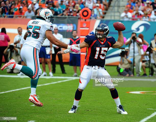 Tim Tebow of the Denver Broncos passes despite pressure by Koa Misi of the Miami Dolphins at Sun Life Stadium on October 23 2011 in Miami Gardens...