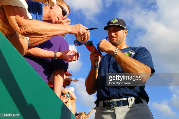 Tim Tebow of the Fireflies signs autographs along the rail near the dugout moments before the start of the minor league game between the Columbia...