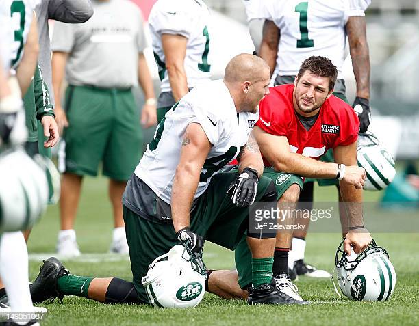 Tim Tebow of the New York Jets talks with Tanner Purdum of the New York Jets at Jets Training Camp at SUNY Cortland on July 27 2012 in Cortland New...