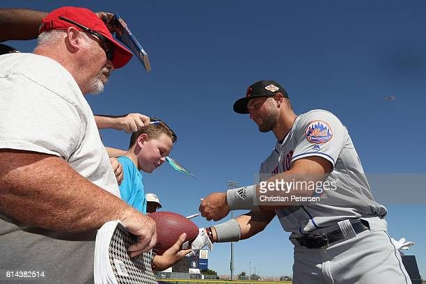 Tim Tebow of the Scottsdale Scorpions signs autographs for fans before the Arizona Fall League game against the Peoria Javelinas at Peoria Stadium on...