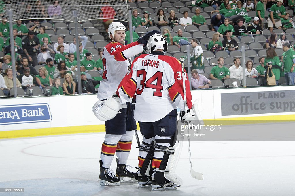 Tim Thomas #34 and <a gi-track='captionPersonalityLinkClicked' href=/galleries/search?phrase=Erik+Gudbranson&family=editorial&specificpeople=5741800 ng-click='$event.stopPropagation()'>Erik Gudbranson</a> #44 of the Florida Panthers celebrate a win against the Dallas Stars in the home opener at the American Airlines Center on October 3, 2013 in Dallas, Texas.