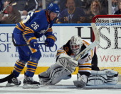 Tim Thomas of the Boston Bruins covers the puck as Thomas Vanek of the Buffalo Sabres looks for a rebound at the HSBC Arena on November 3 2010 in...