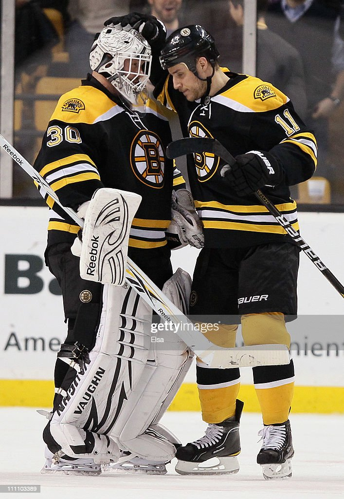 Tim Thomas of the Boston Bruins is congratulated by teammate Gregory Campbell after Thomas shut out the Chicago Blackhawks on March 29 2011 at the TD...