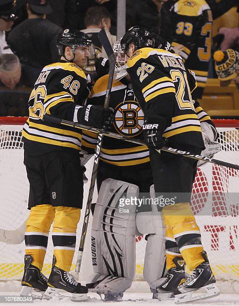 Tim Thomas of the Boston Bruins is congratulated by teammates David Krejci and Blake Wheeler after the game against the Washington Captials on...