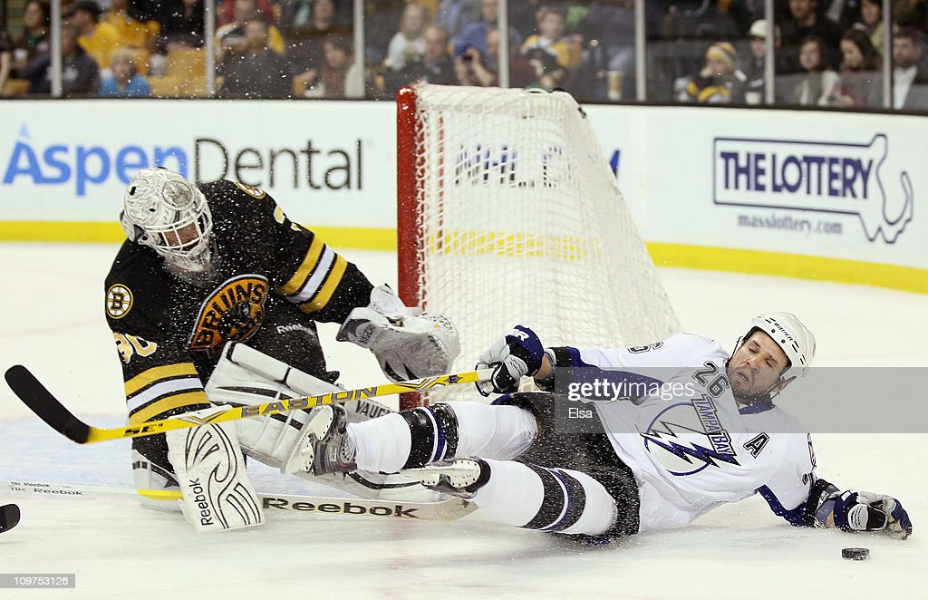 Tim Thomas #30 of the Boston Bruins stops a shot as Martin St. Louis #26 of the Tampa Bay Lightning runs into him in the second period on March 3, 2011 at the TD Garden in Boston, Massachusetts.